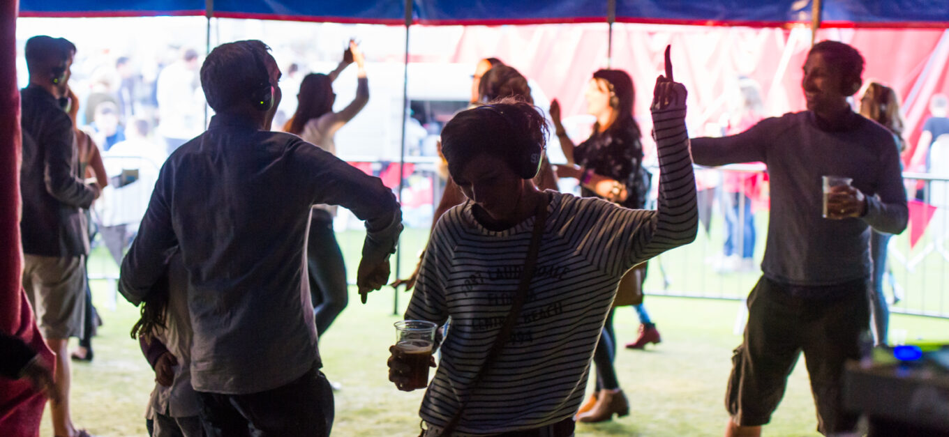 People dance while listening to headphones in a festival tent at Head For The Hills